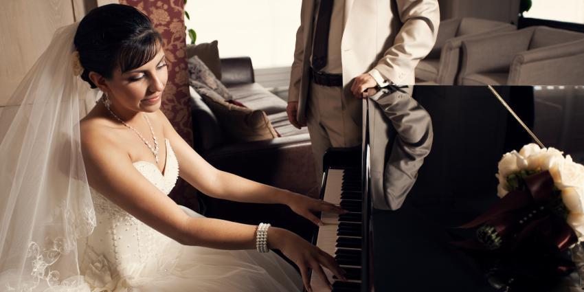Braut spielt auf Klavier, Bräutigam steht dahinter