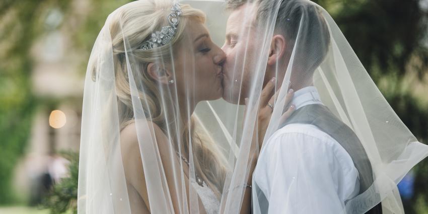 Brautpaar küsst sich unter Schleier der Braut